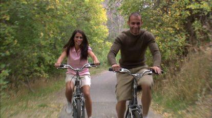 فوتیج دوچرخه سواری یک زوج در جاده پر از درخت