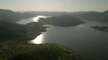 فوتیج هوایی بازتاب نور روی آب در چشمانداز کوهستانی