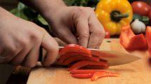فوتیج مرد در حال بریدن فلفل در میان سبزیجات