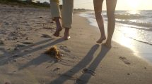 فوتیج کلوزاپ از قدم زدن یک زوج در کنار ساحل