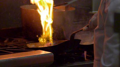 فوتیج ویدیویی اسلوموشن آشپز در حال پختن غذا روی شعله