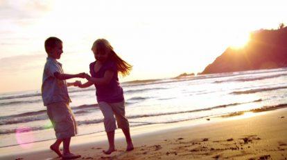 فوتیج ویدیویی اسلوموشن رقصیدن دو کودک کنار ساحل در هنگام غروب