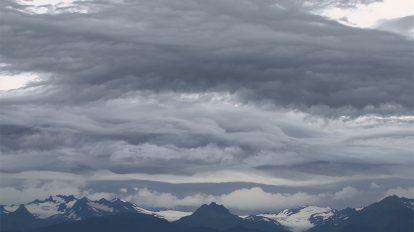 فوتیج ویدیویی حرکت موجی ابرها بالای کوه ها در آسمان